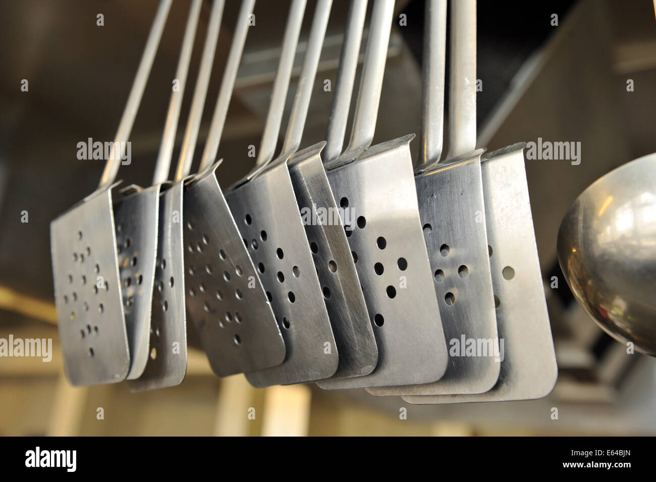 Spatulas hanging up in Catering College, Bradford - Stock Image
