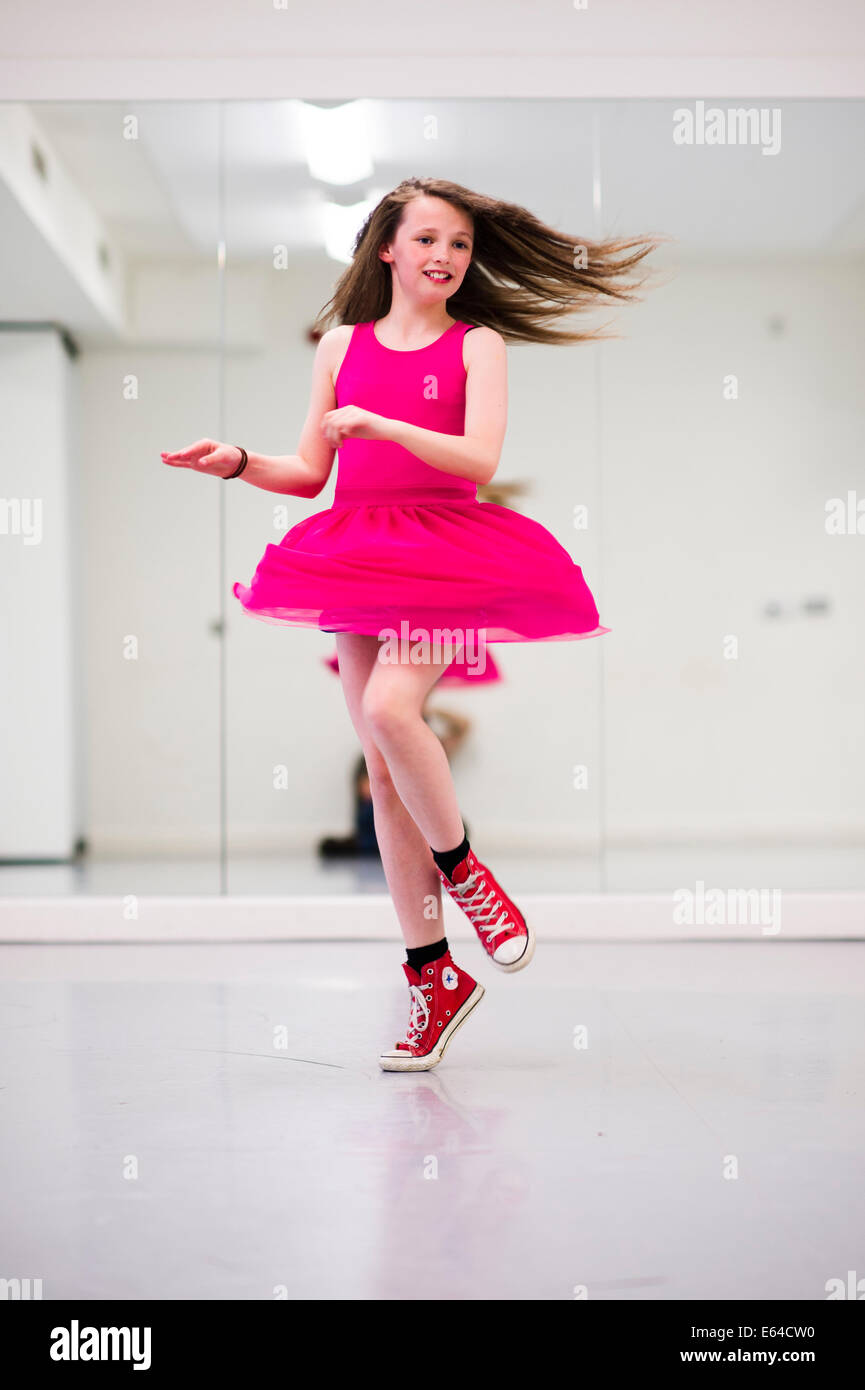 fa8bb07a705864 A dancing spinning 10 year old pre teenage girl in a dance studio wearing a  pink dress and red converse boots UK
