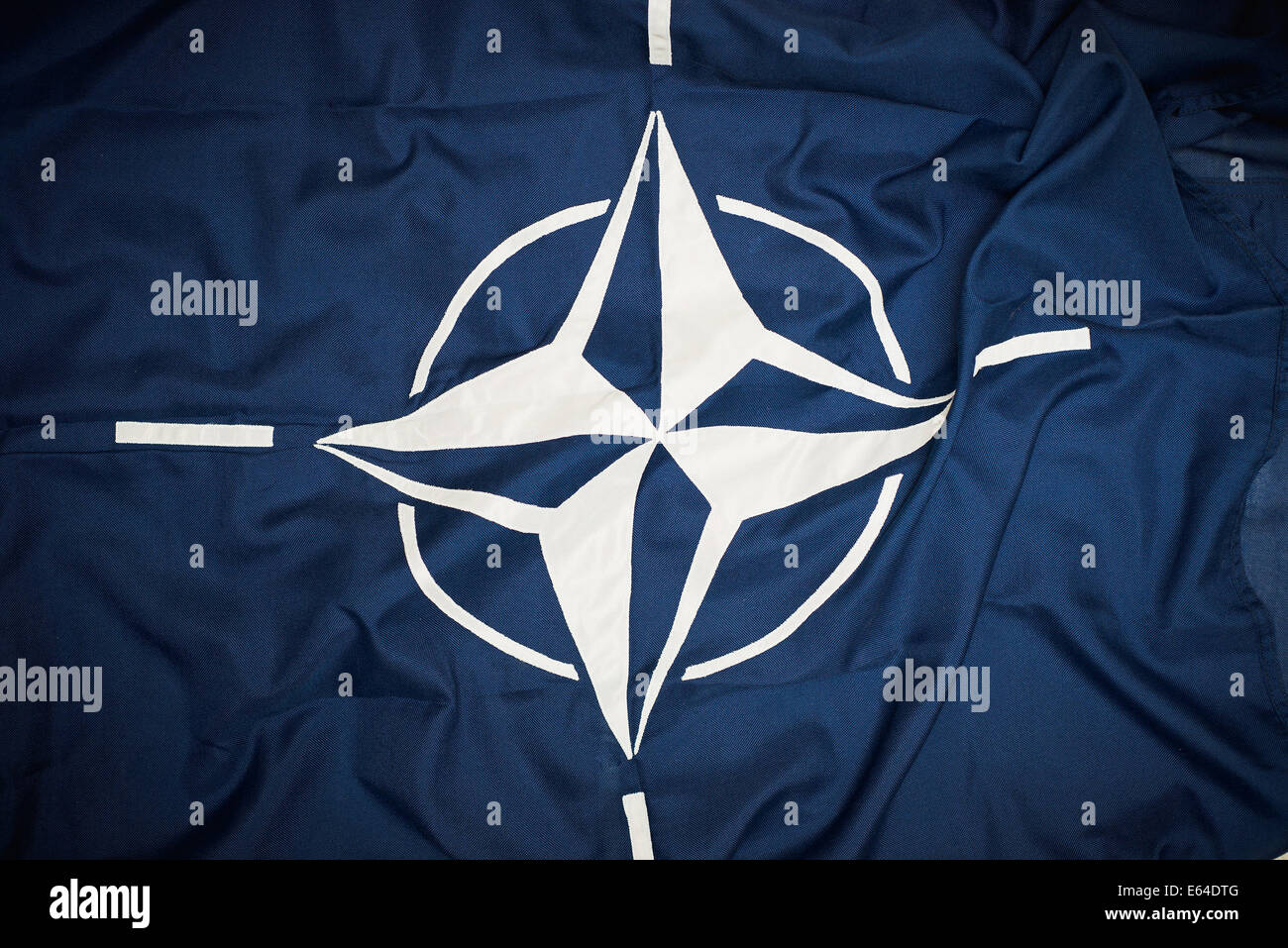 The flag of the North Atlantic Treaty Organization (NATO) consists of a dark blue field charged with a white compass Stock Photo
