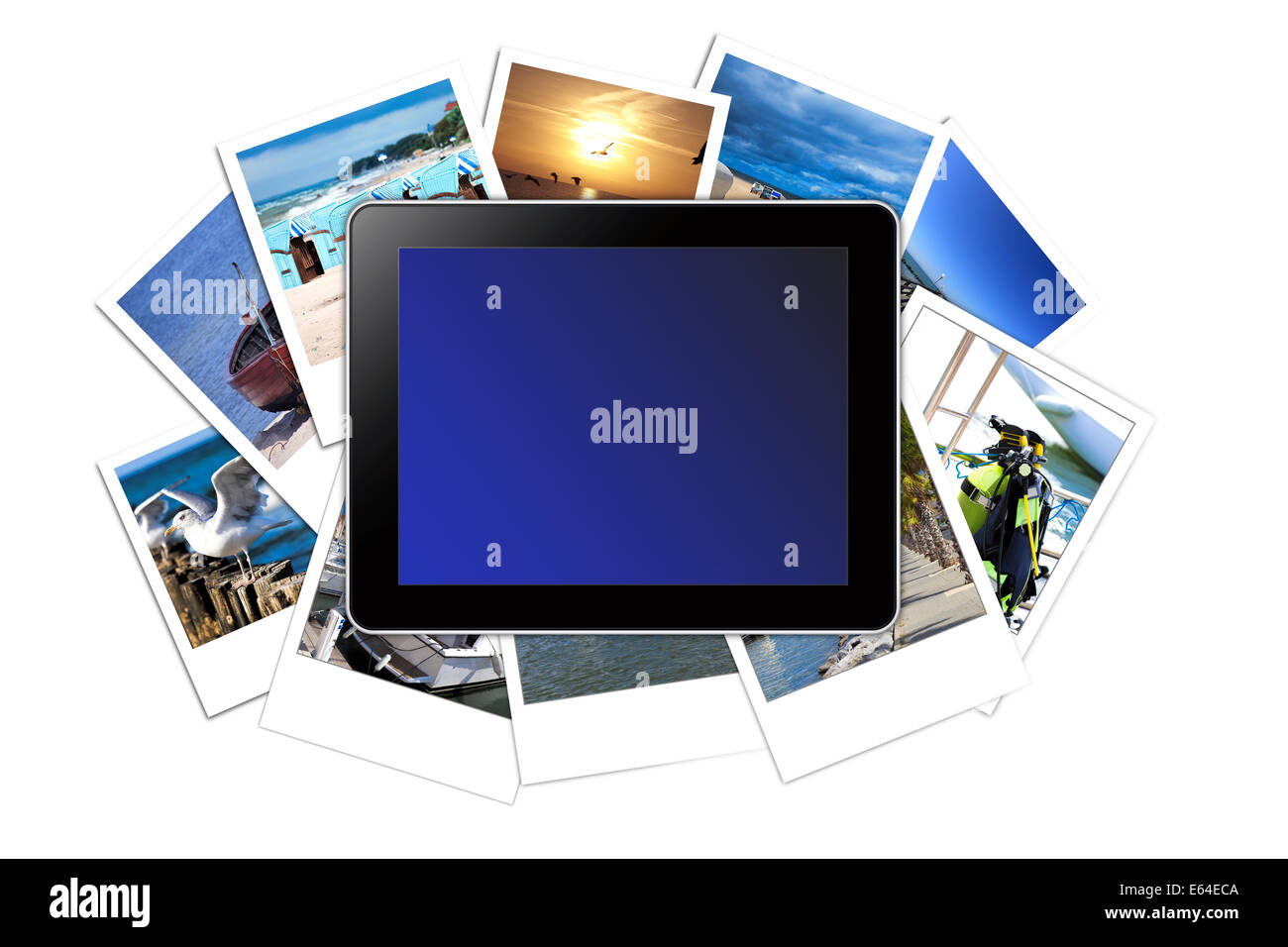 Digital Tablet with blank Display lies on a stack of many Vacations instant pictures isolated on white Background - Stock Image