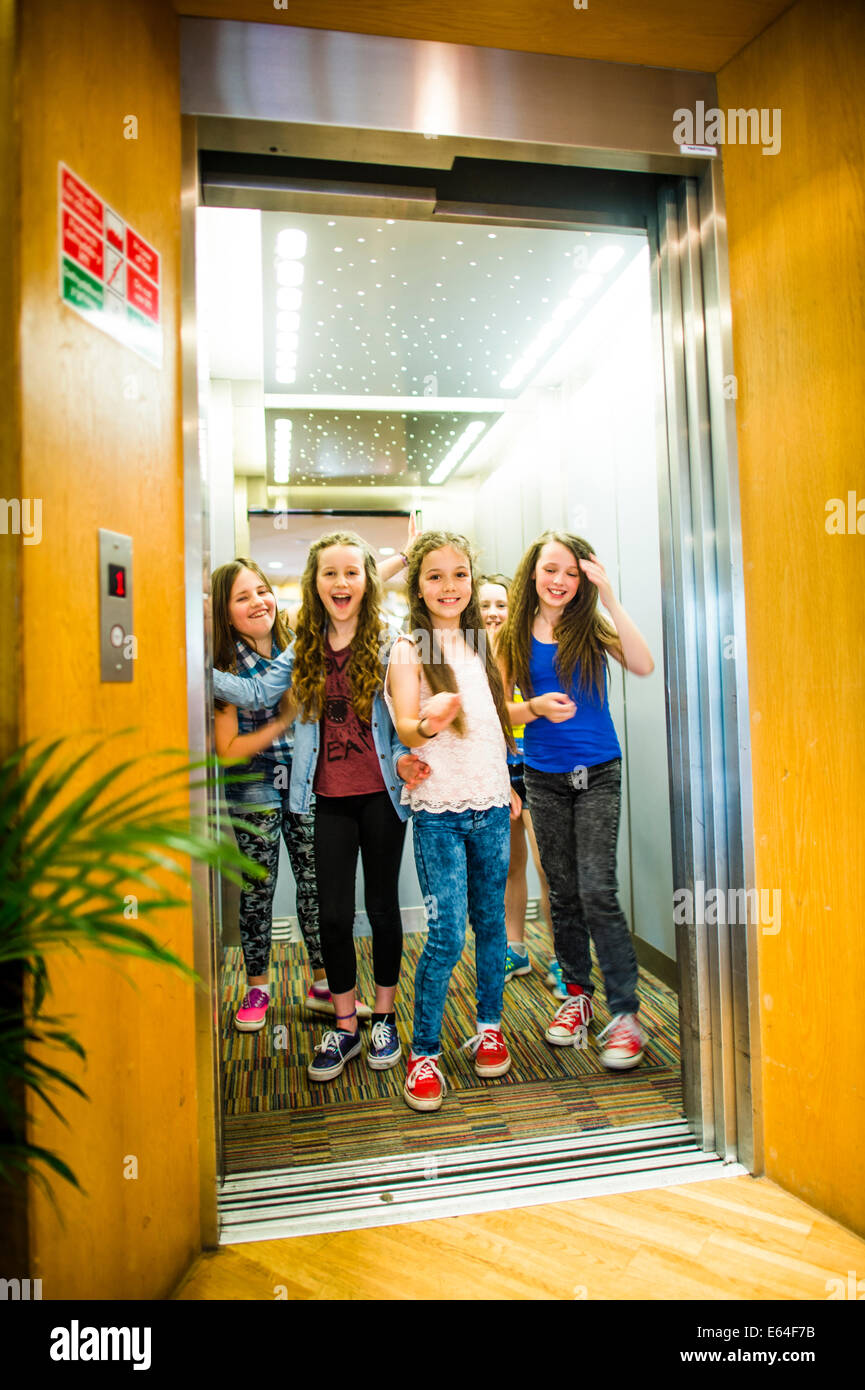 A group of 5 five 10 year old pre teenage girls friends together in a lift elevator  UK - Stock Image
