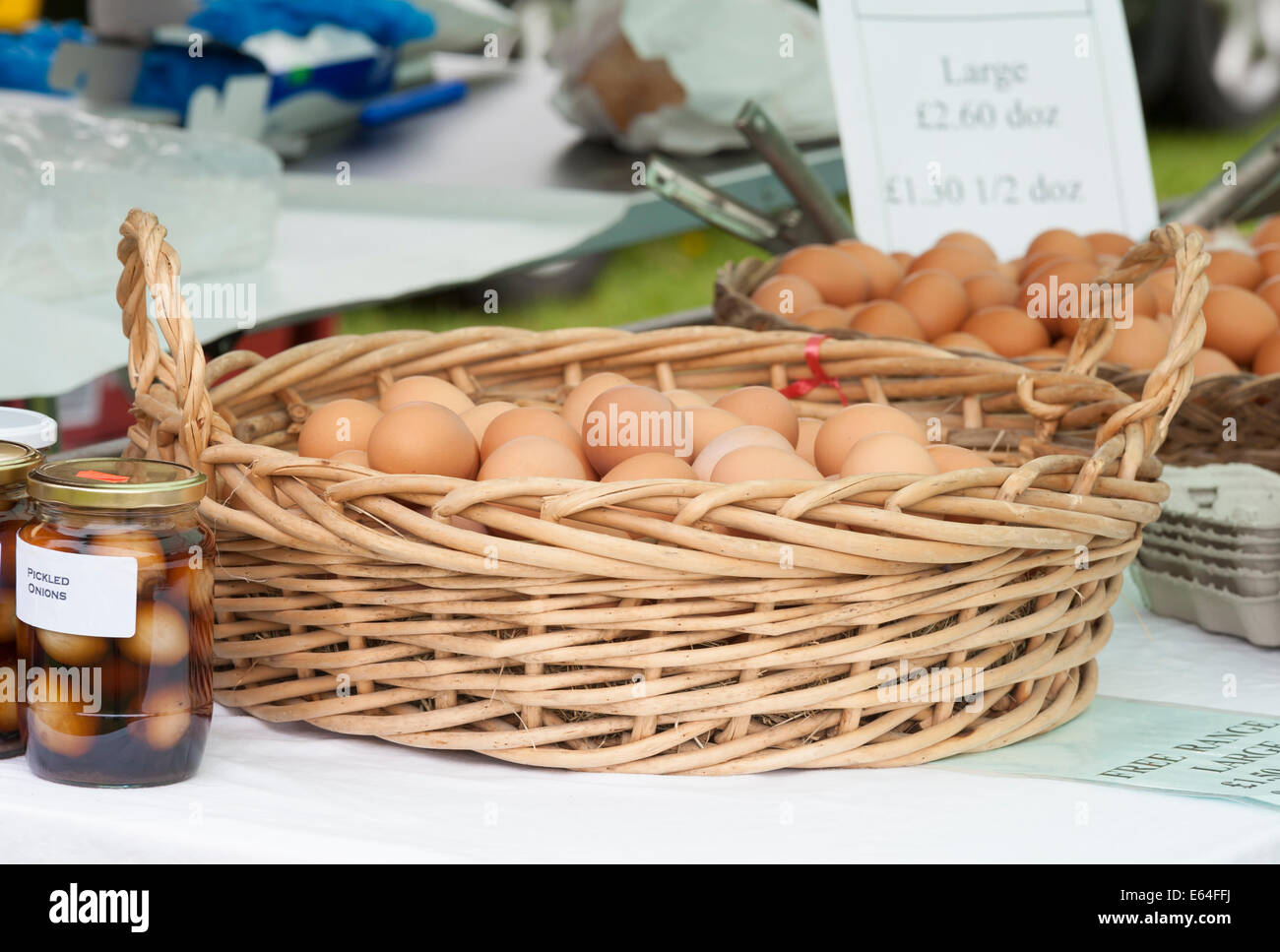 A wicker basket containing large free range hens eggs and pickles eggs for sale on a market stall - Stock Image