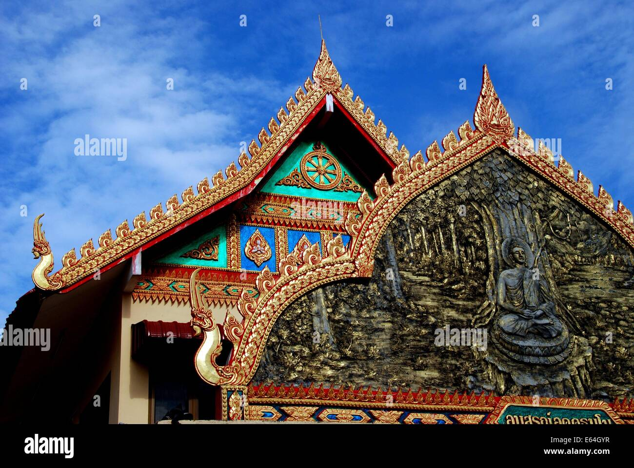 GEORGETOWN, MALAYSIA: Bas relief panel with Buddha and opulent roofs at Thai Wat Buppharam Stock Photo