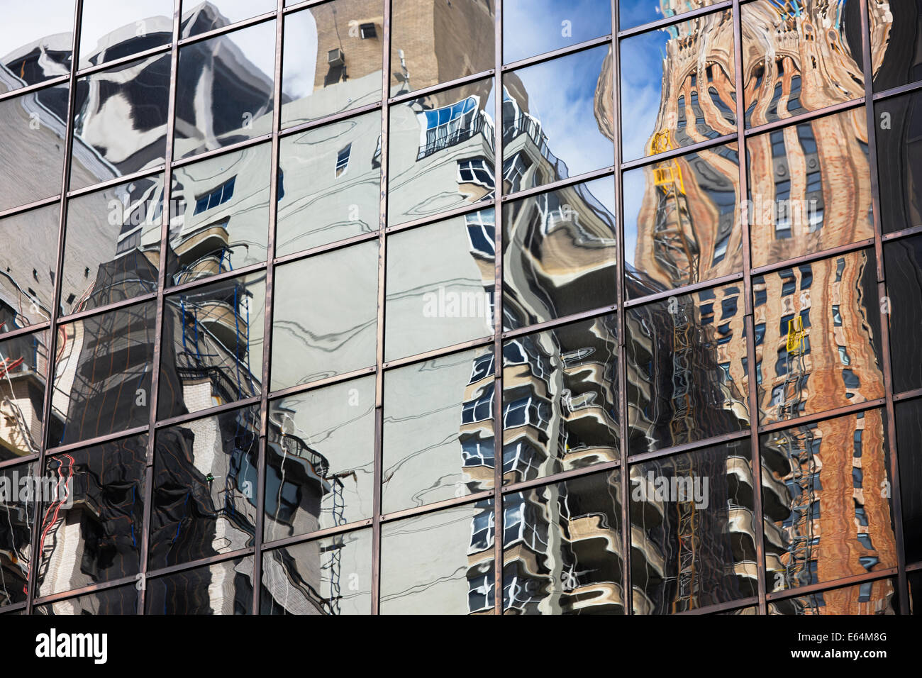 Distorted reflections of high-rise buildings in a glass wall of another highrise on Manhattan. New York, USA. Stock Photo