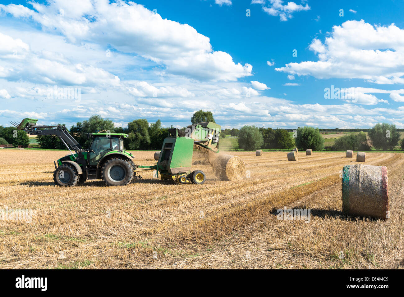 tractor throwing out hay roll - Stock Image