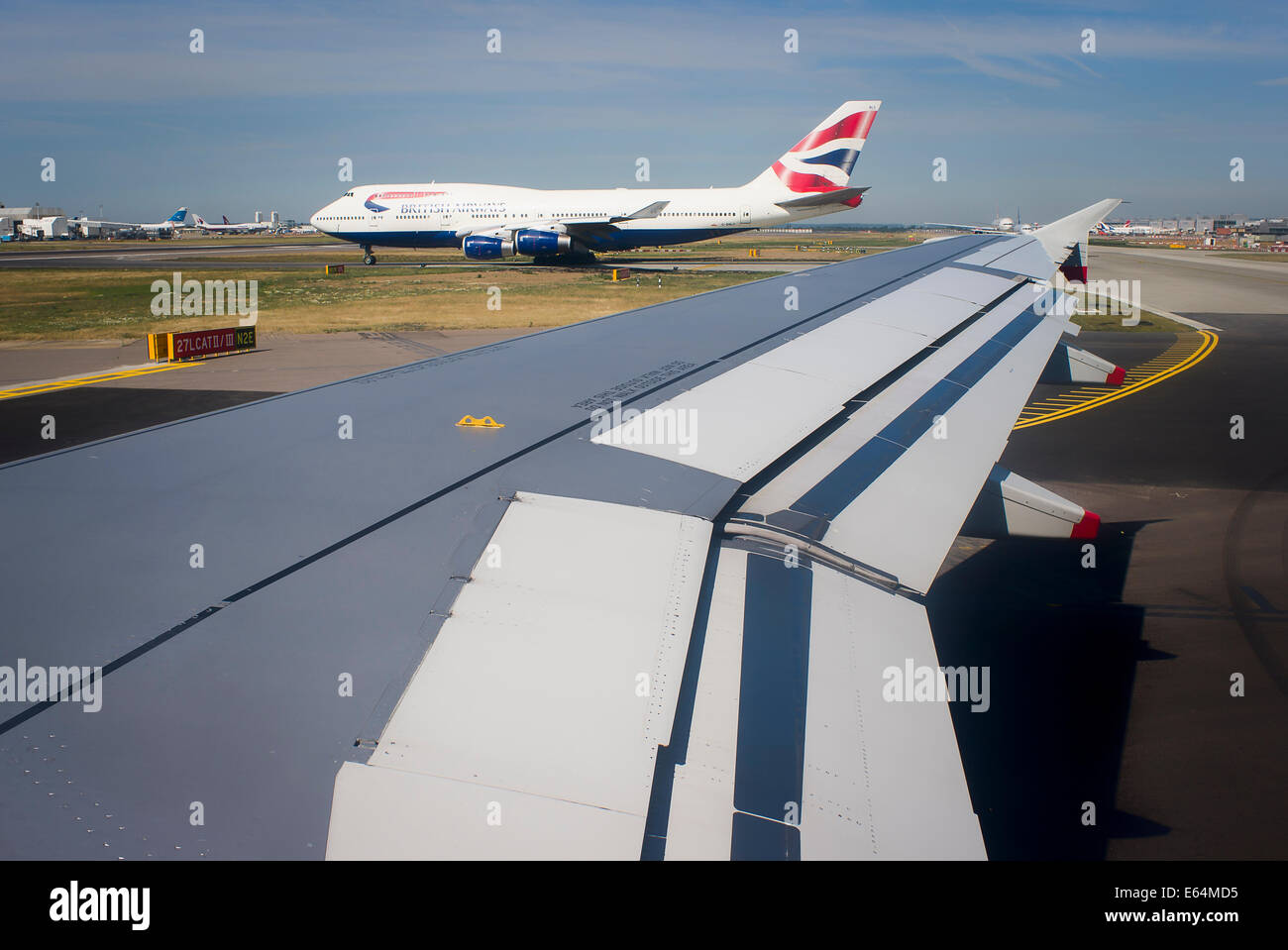 Wings of flight. View of airfileld with aircraft taxying in UK - Stock Image
