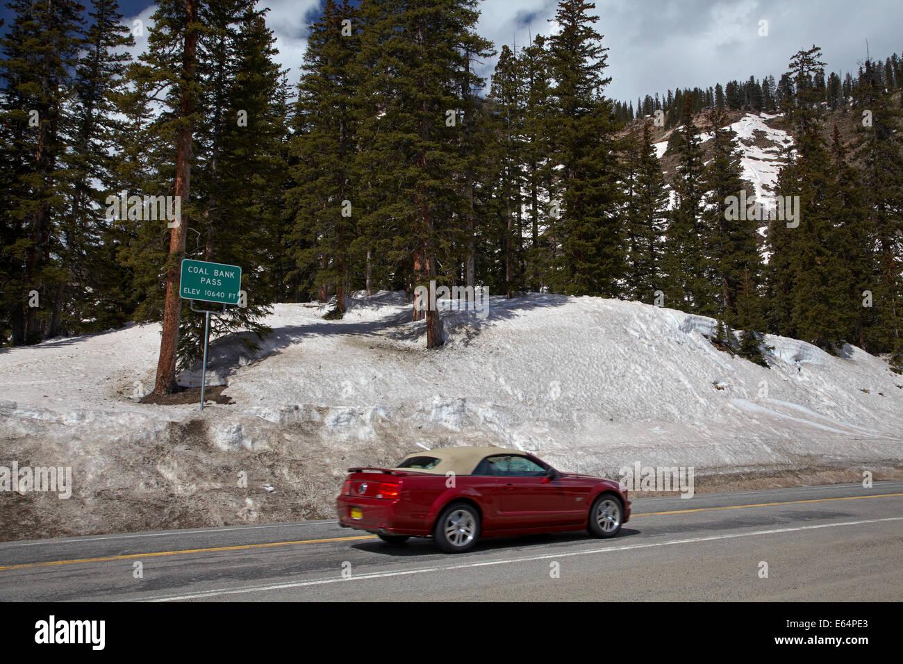 Mustang convertible at summit of Coal Bank Pass (10,640 ft./3243 m), US 550, San Juan Skyway, Colorado, USA - Stock Image