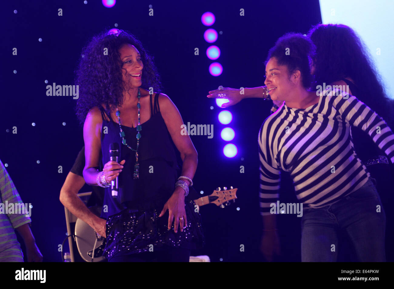 A Newham resident joins​sisters Debbie, Kim, Joni​ on the stage for the annual ​Under the Stars concert in Newham. - Stock Image