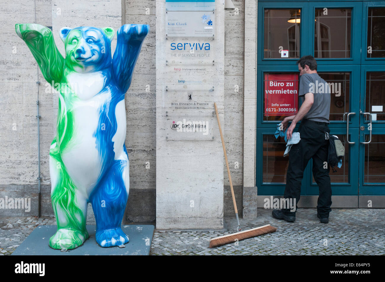 A cleaner at work at the entrance to a bank branch in Berlin.  The bear recalls the heraldic emblem of the city. - Stock Image
