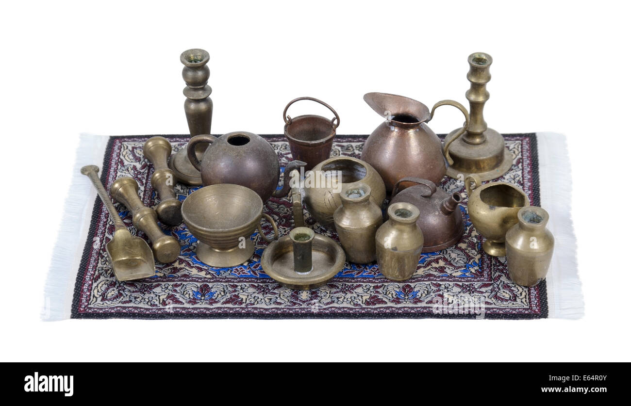 A variety of different junk items just as pots and pans and candlesticks on fancy rug - path included Stock Photo