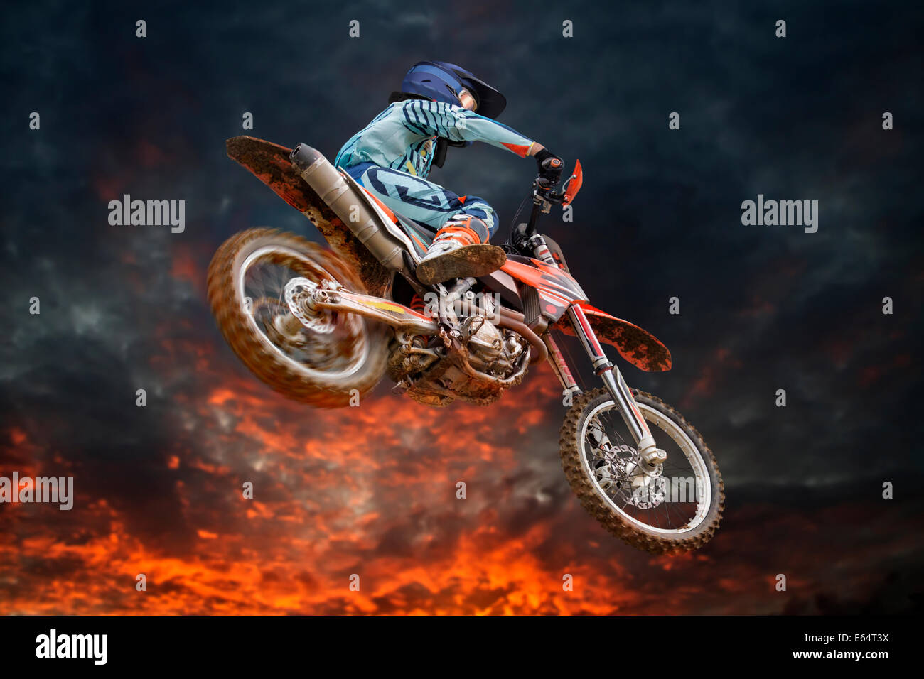 Jumping motocross rider with firestorm in the background and red glowing spinning rear wheel - Stock Image