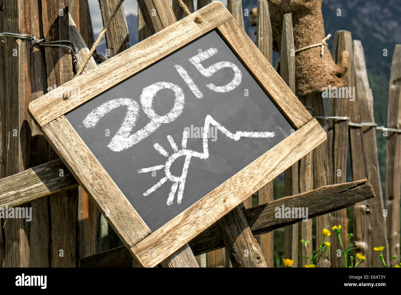 Wooden palisade with chalkboard hint panel. Chalkboard with 2015 date - Stock Image