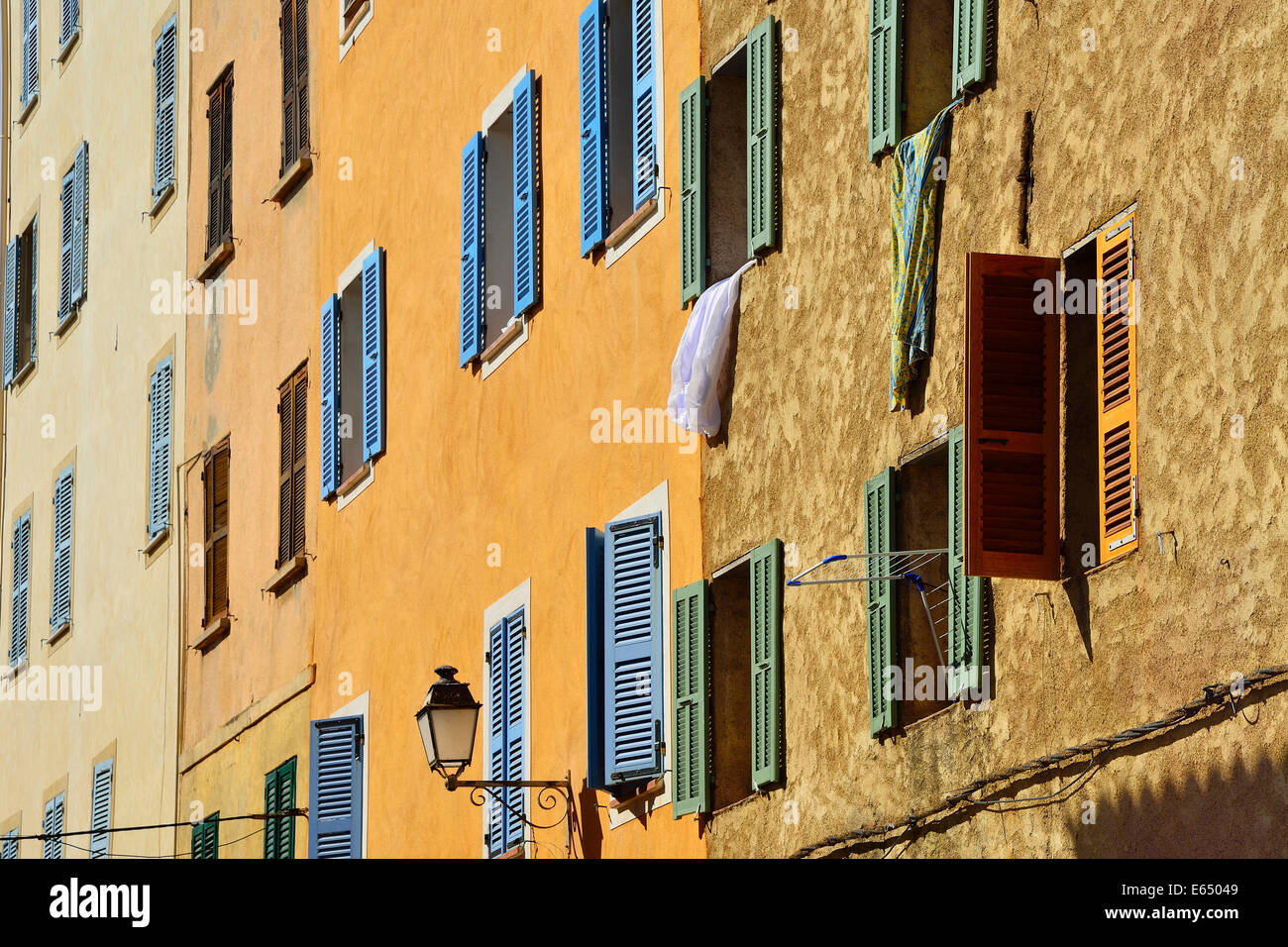 Row of houses with colourful shutters, L'Île Rousse, Balagne, Corsica, France Stock Photo