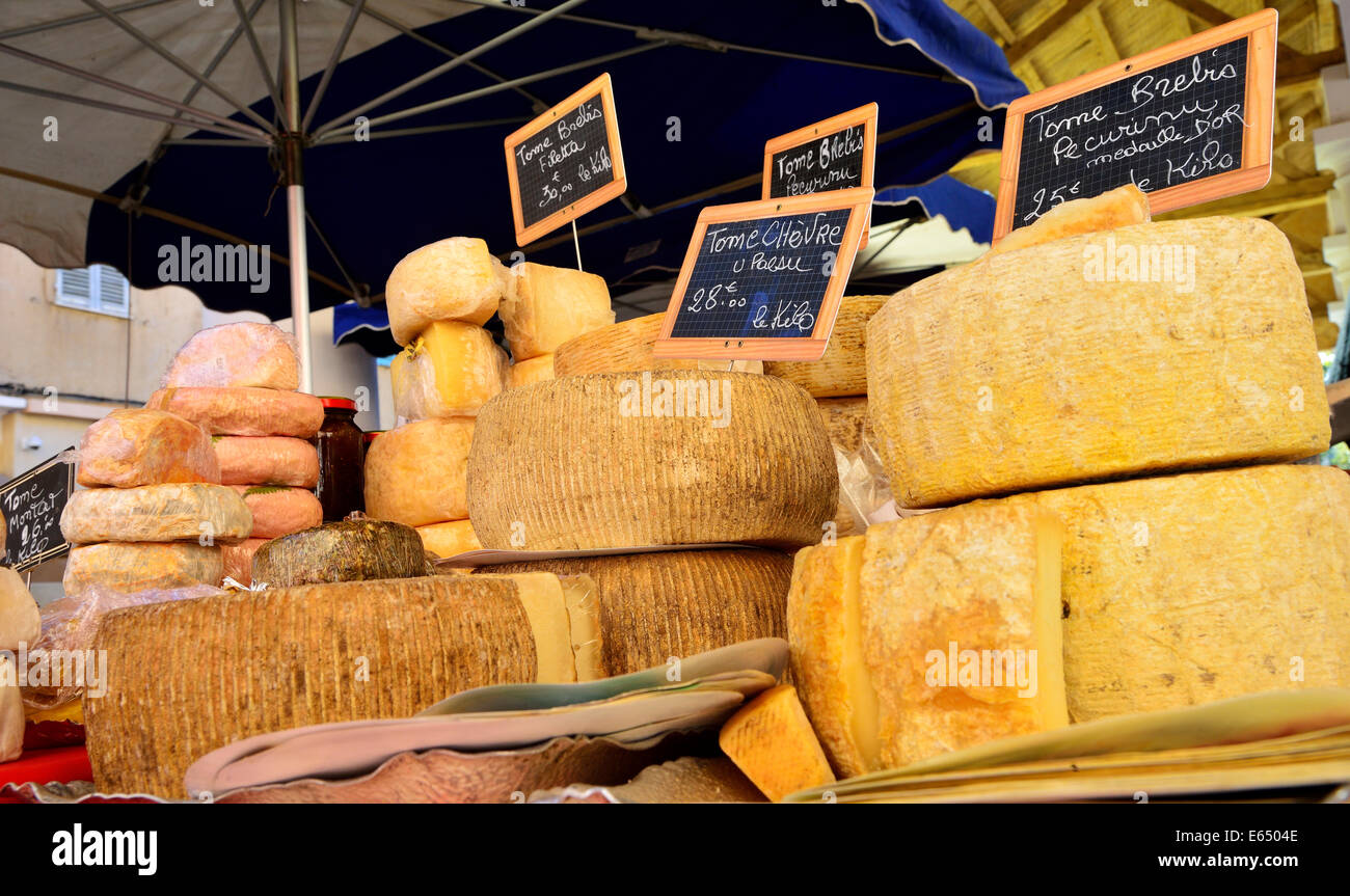 Various types of cheeses at a market stall, L'Île-Rousse, Balagne, Corsica, France - Stock Image