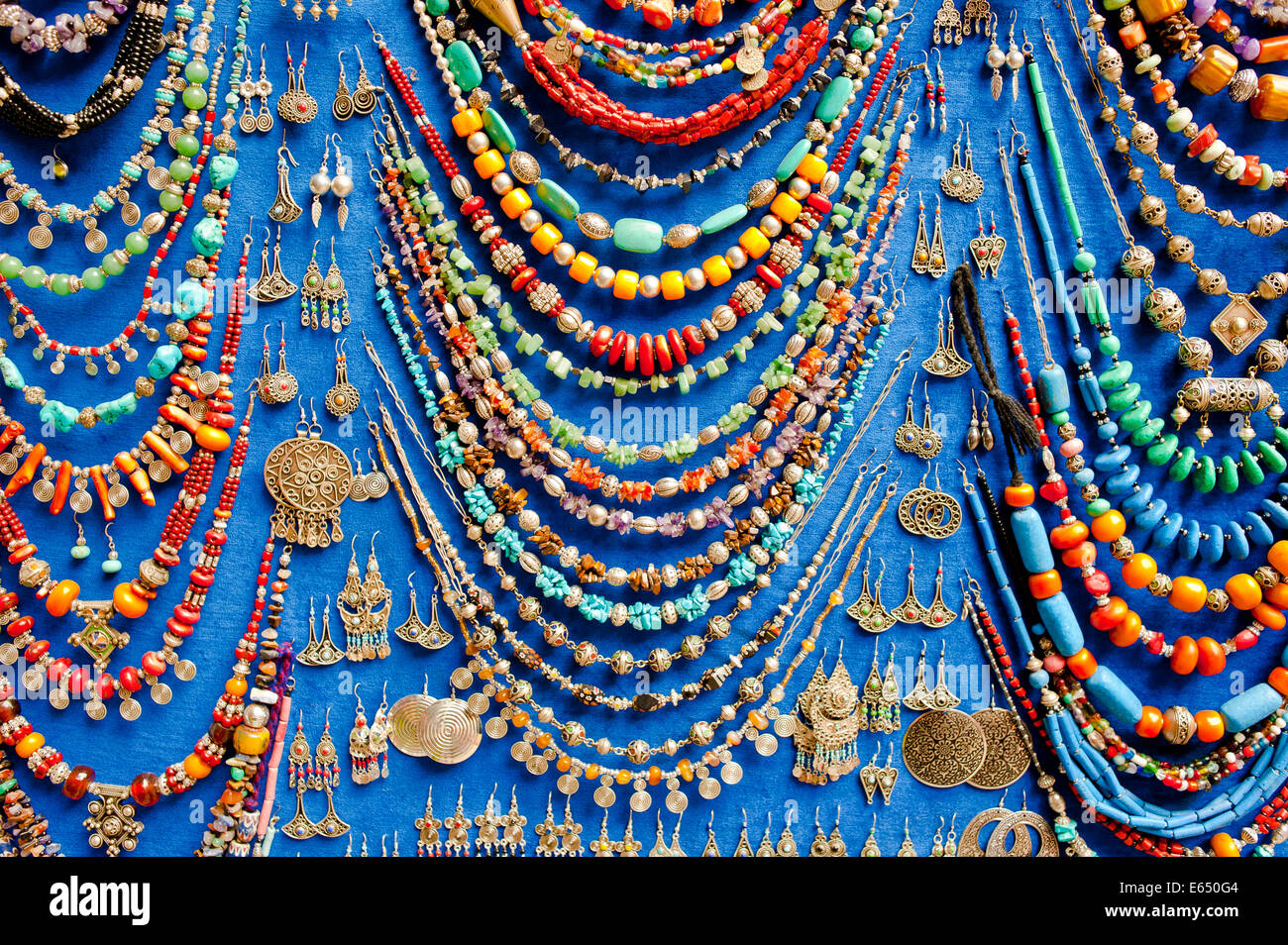 Display of various necklaces and earrings with glass beads and traditional Arab and Berber patterns - Stock Image