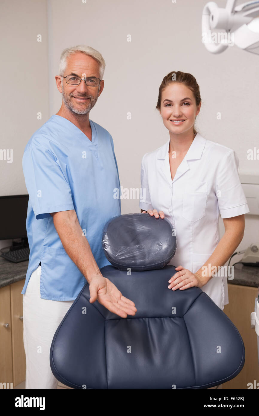 Dentist and assistant smiling at camera inviting you to the chair - Stock Image