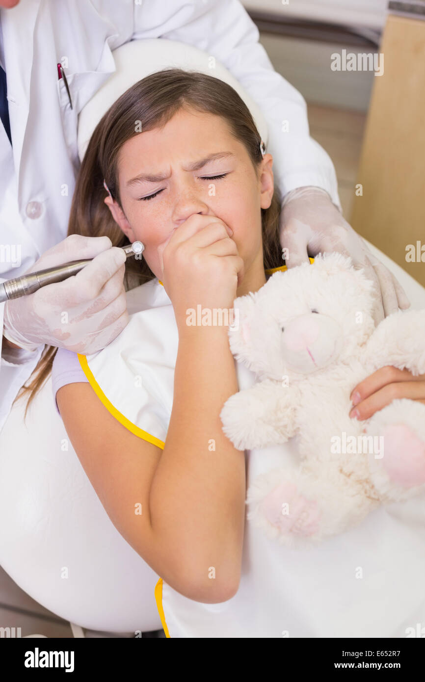 Pediatric dentist trying to see coughing patients teeth - Stock Image