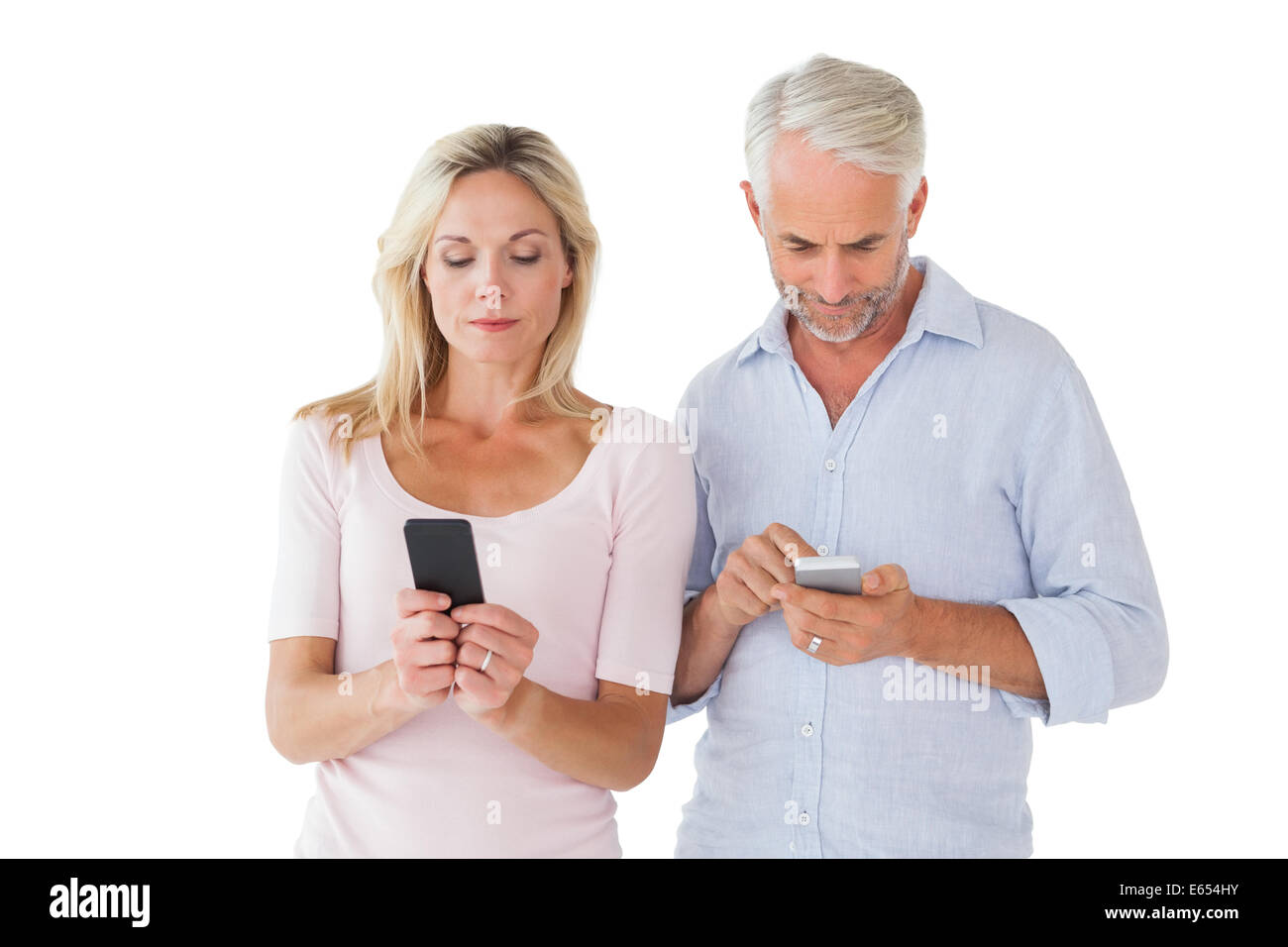 Happy couple texting on their smartphones - Stock Image