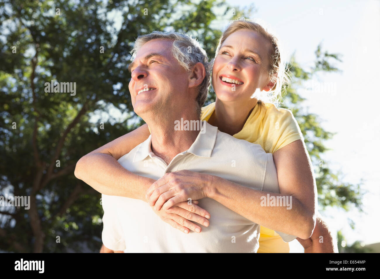 Happy senior man giving his partner a piggy back - Stock Image