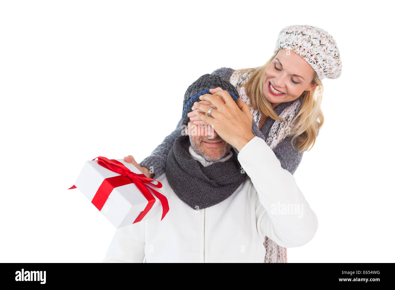 Happy woman holding gift while covering husbands eyes - Stock Image