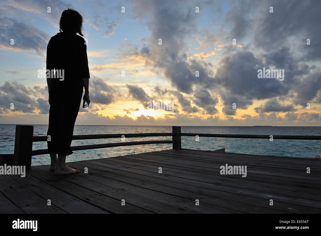 Woman silhouette - woman contemplating the sunrise, Island of Borneo, Sabah State, Malaysia - Stock Image