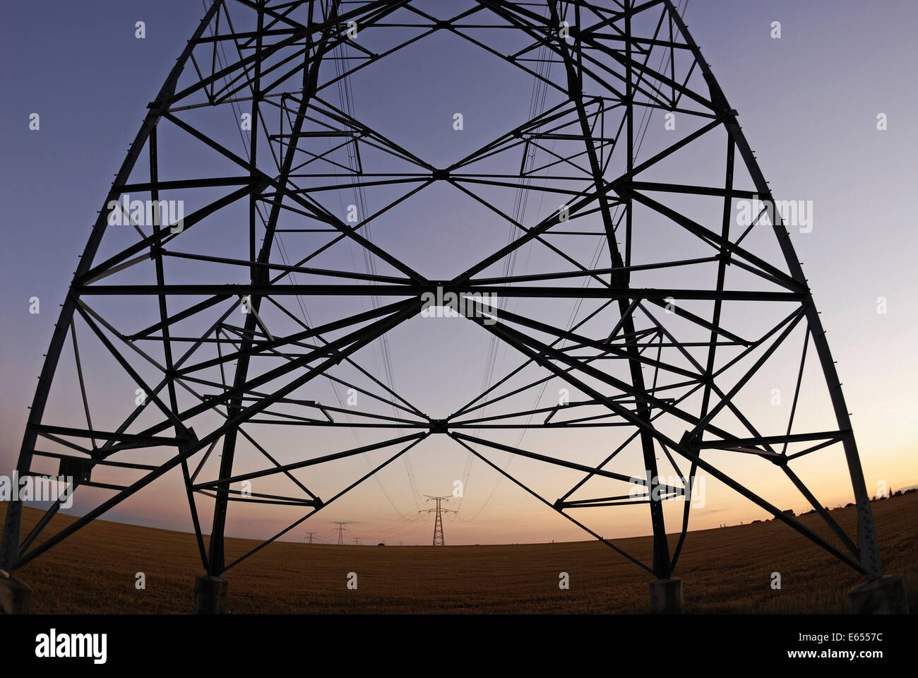 Electricity pylons at sunset, france - Stock Image