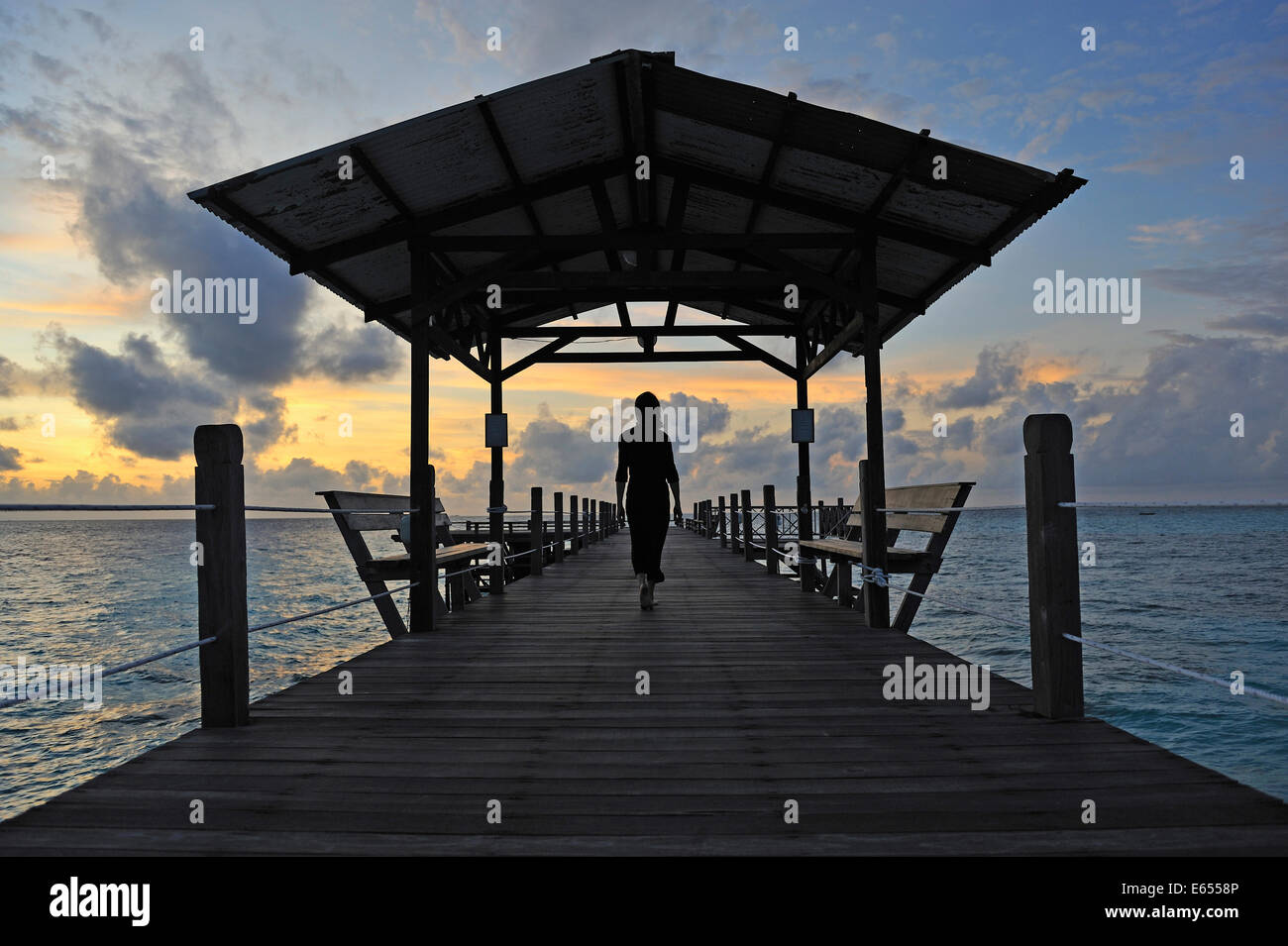 Woman walking on wooden jetty at sunrise, Island of Borneo, Sabah State, Malaysia, Southeast Asia - Stock Image