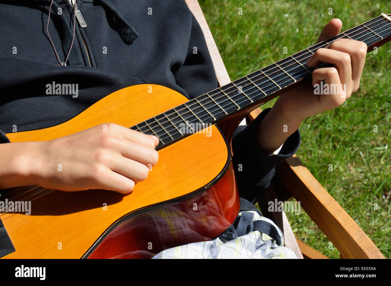 Teenage boy playing acoustic guitar outdoors - Stock Image