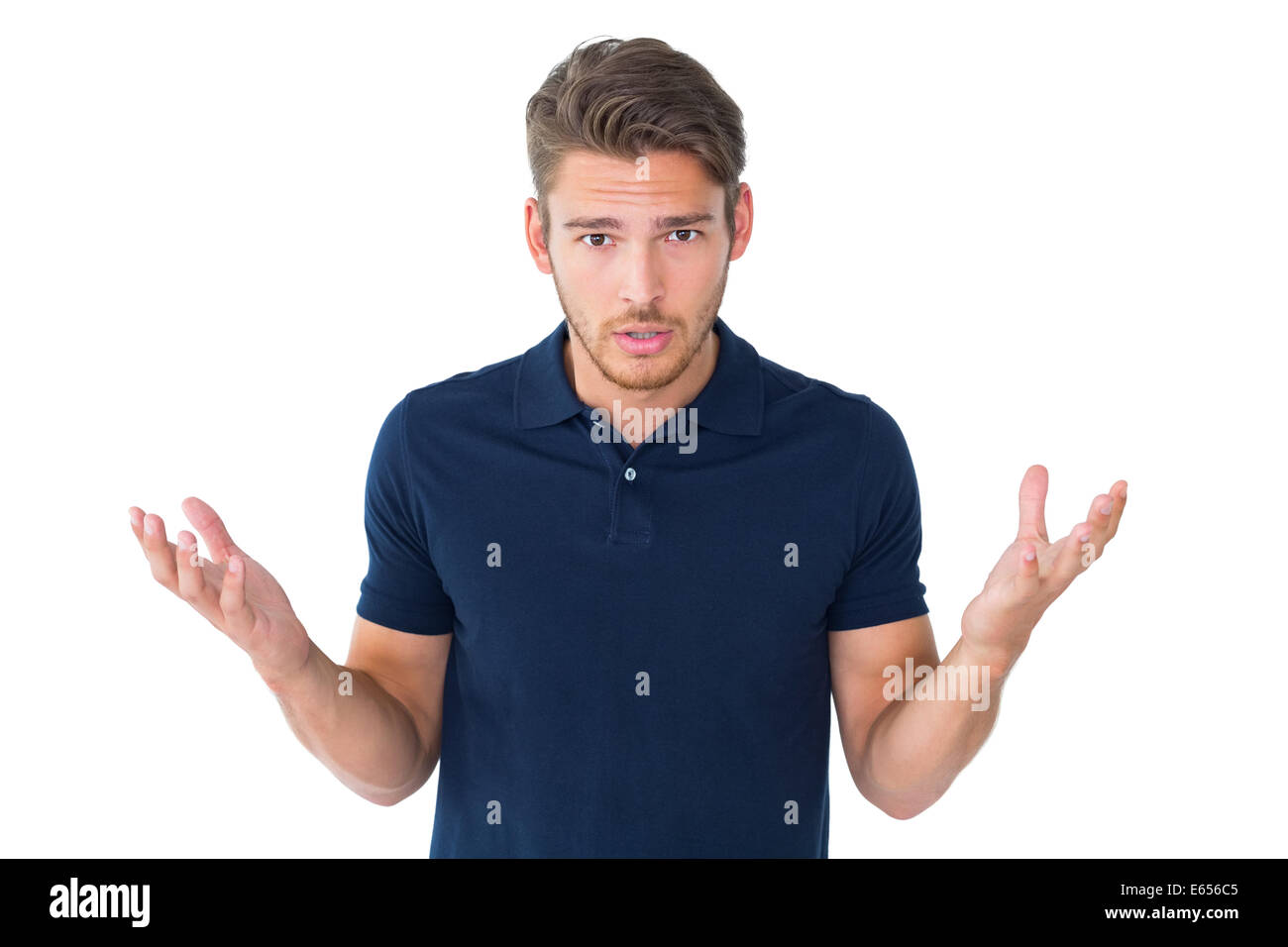 Handsome young man shrugging shoulders - Stock Image