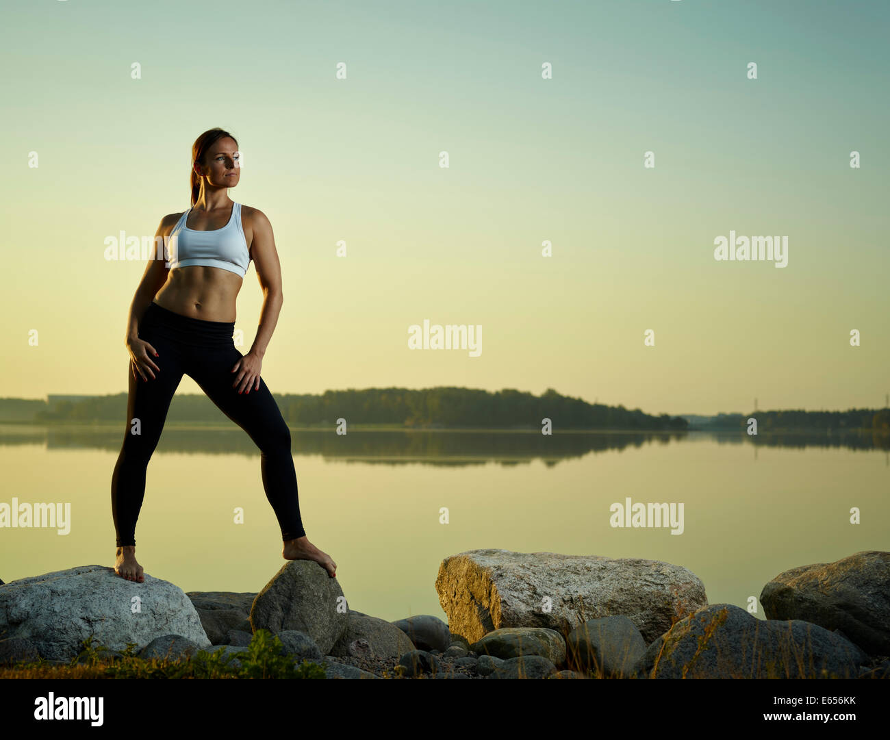 The beautiful young woman exercise yoga early at morning, calm sea on background - Stock Image