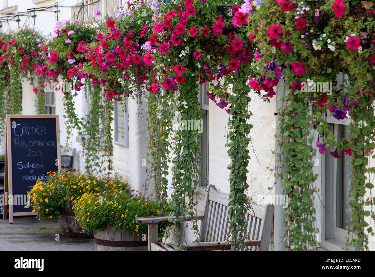 A row of hanging baskets at The Red Lion pub in Cricklade in the Wiltshire Cotswolds, England. - Stock Image