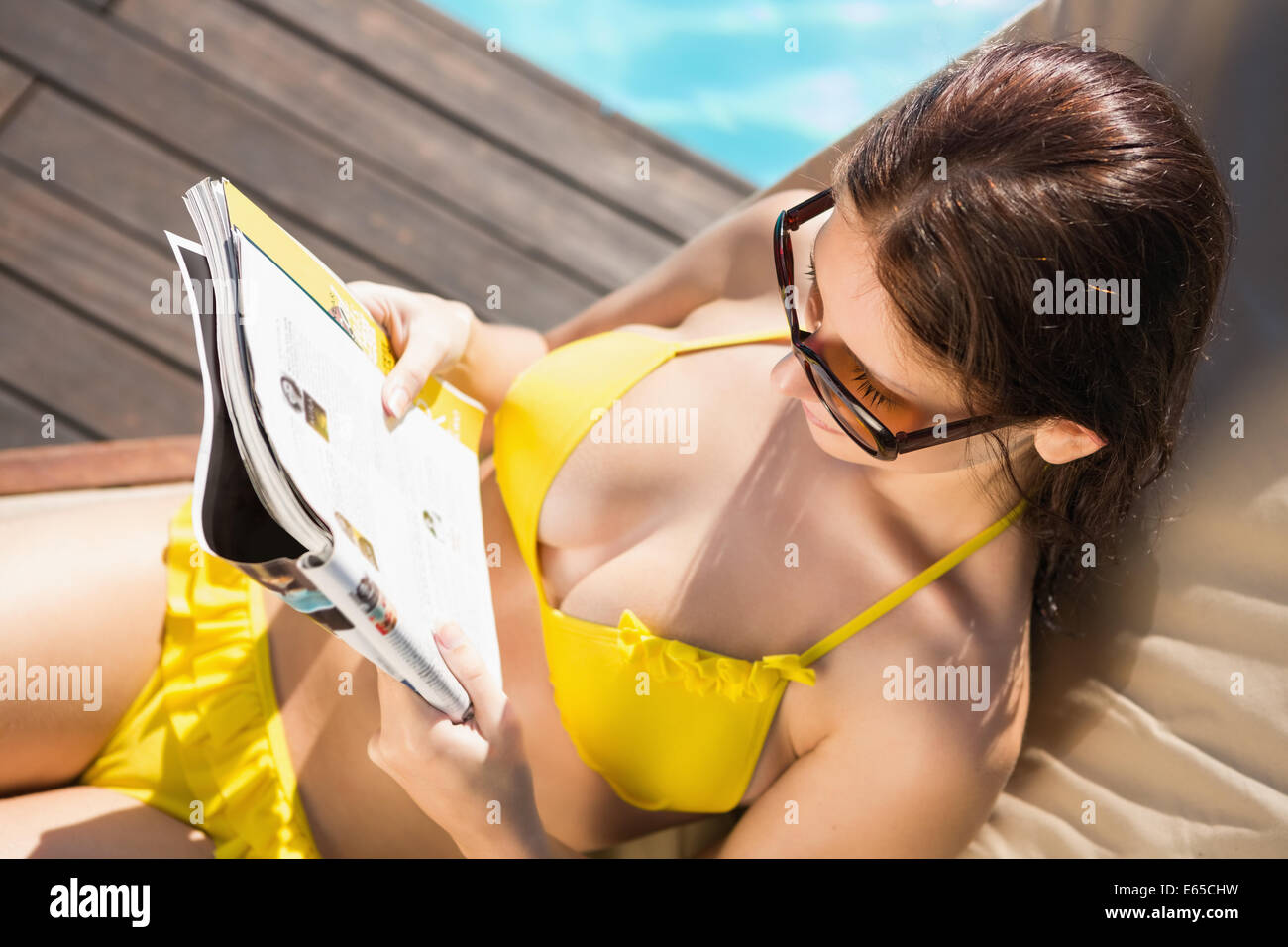 Woman reading book on sun lounger by swimming pool - Stock Image