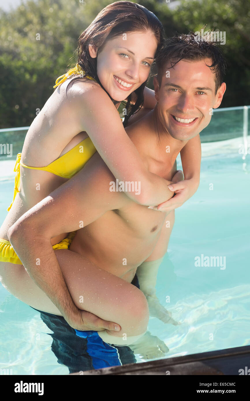 Man carrying cheerful woman by swimming pool - Stock Image