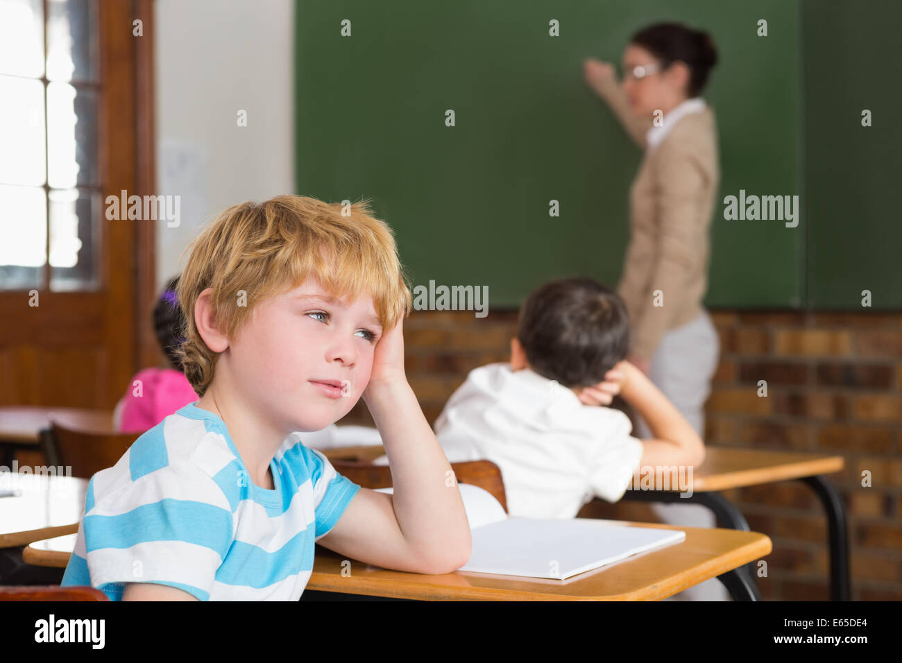 Cute pupil not paying attention in classroom - Stock Image