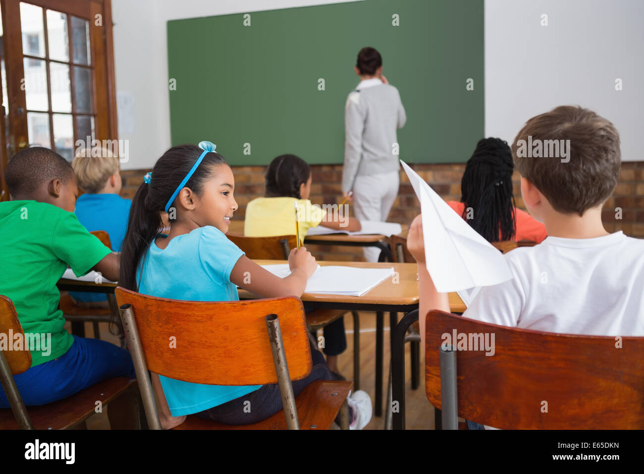 Naughty pupil about to throw paper airplane in class Stock Photo