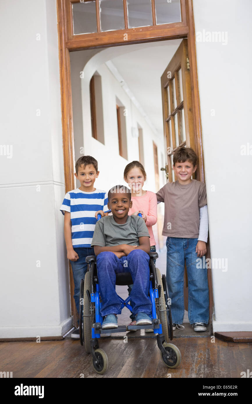 Disabled pupil with his friends in classroom - Stock Image