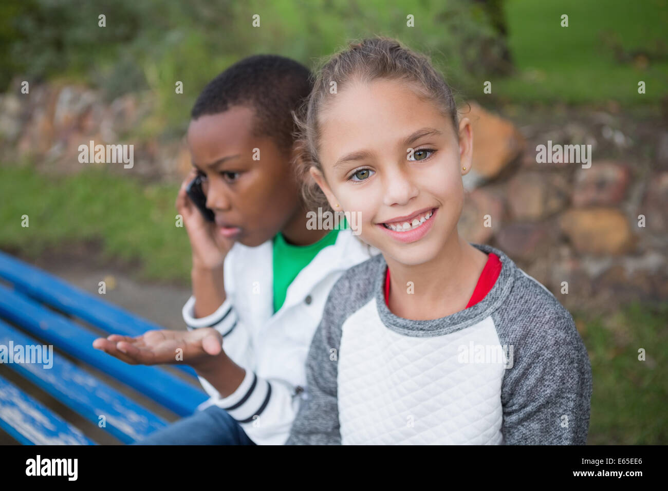 Cute little girl smiling at camera while friend talks on phone - Stock Image
