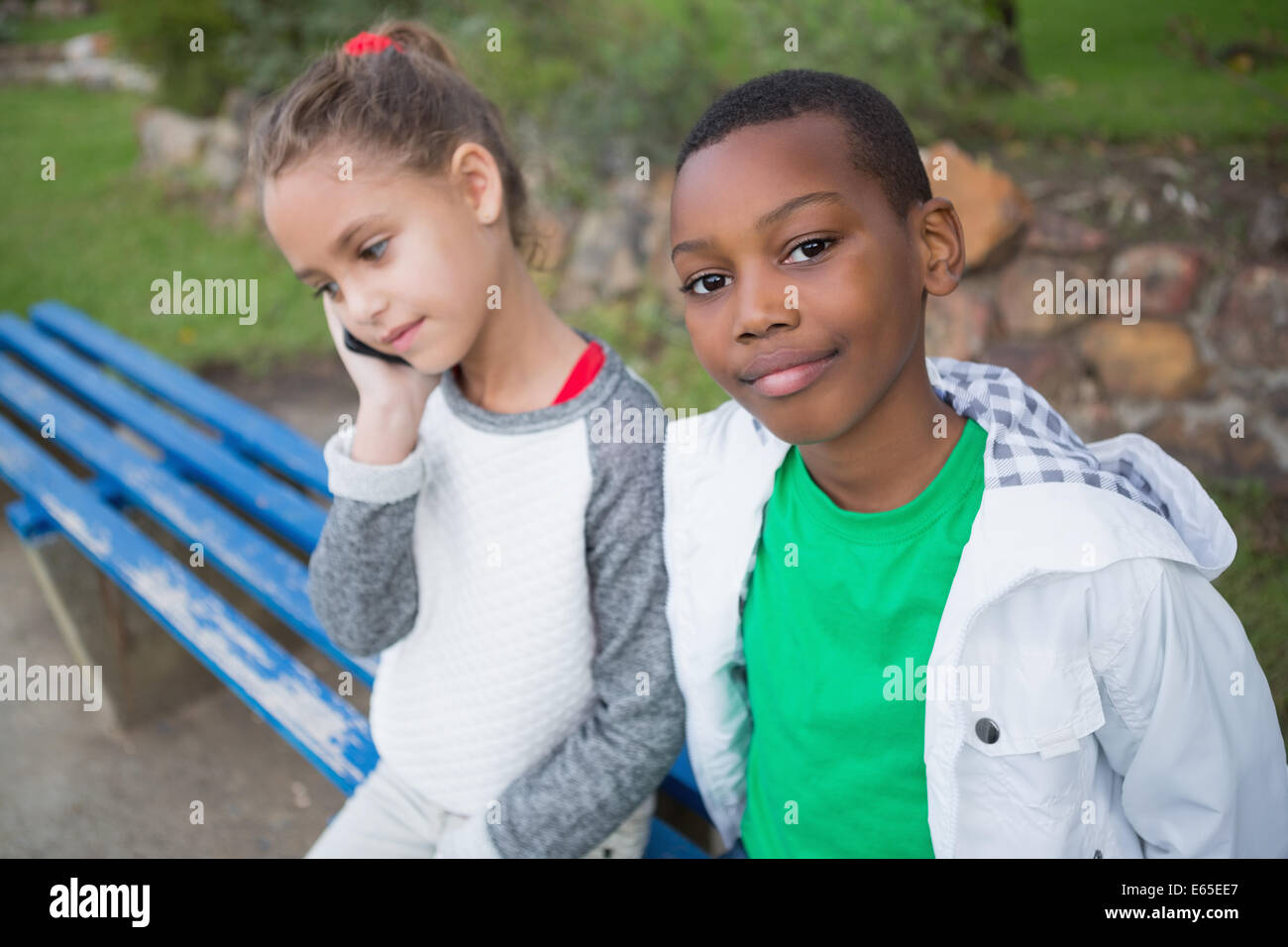 Cute little boy smiling at camera while friend talks on phone - Stock Image