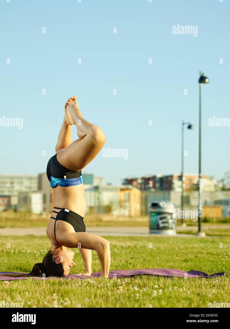 Active fitness woman working out in the park early in the morning, urban background - Stock Image