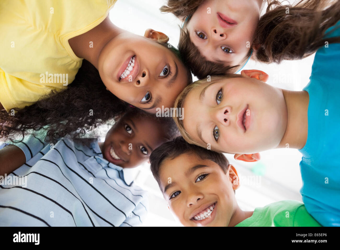 Cute schoolchildren smiling at camera from above - Stock Image