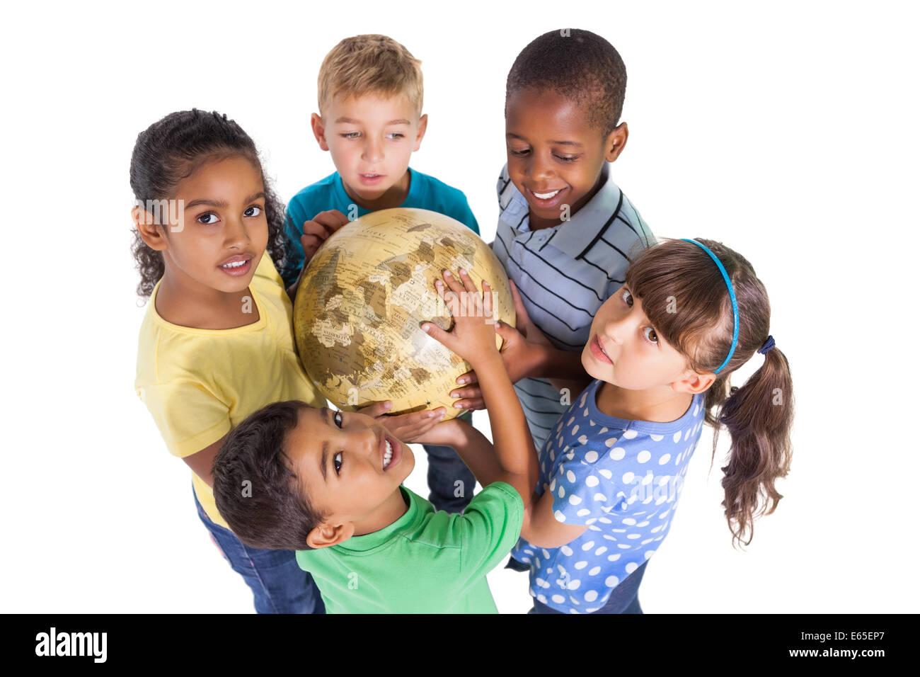 Cute schoolchildren smiling at camera holding globe - Stock Image