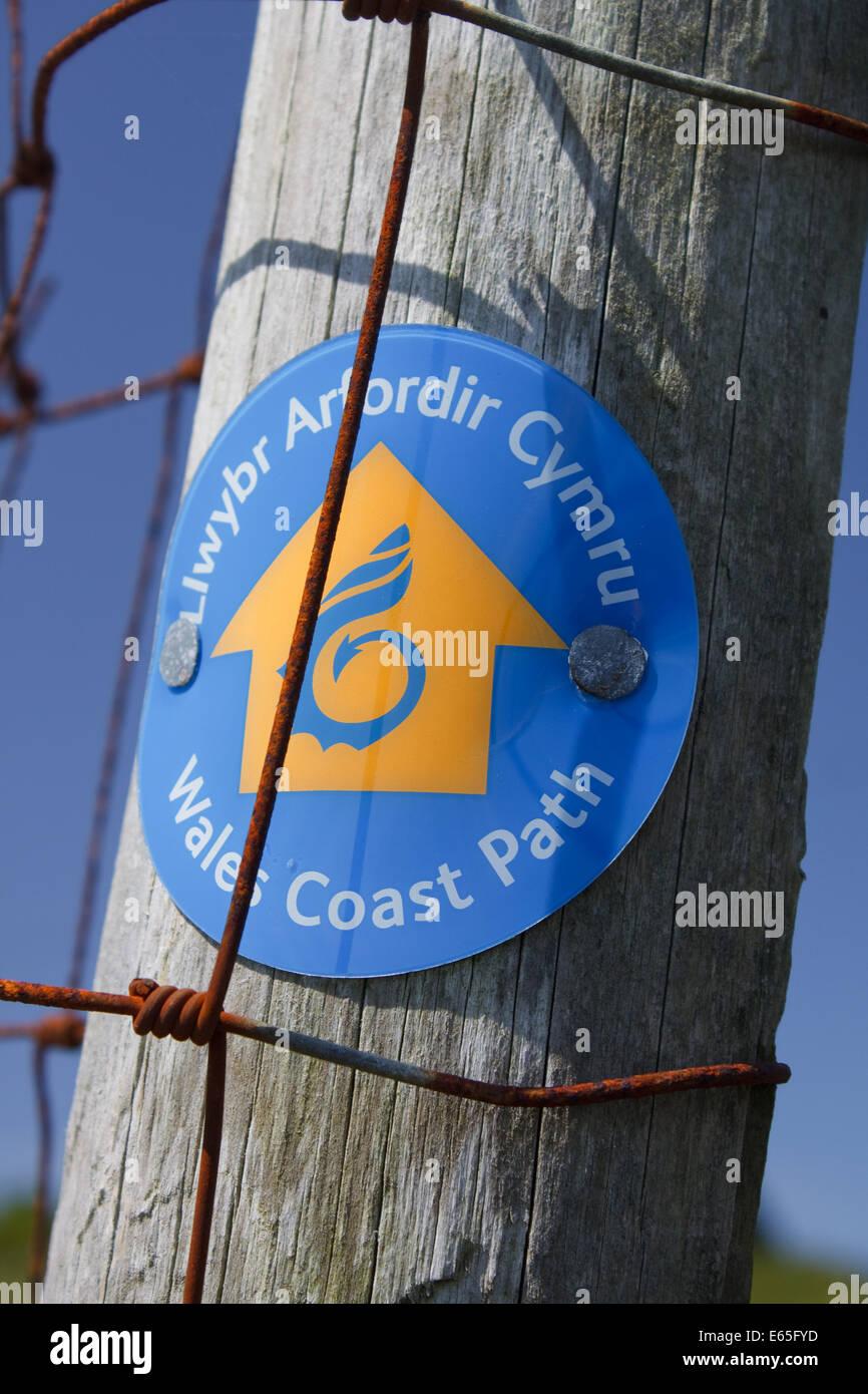 A sign for the Wales Coast Path, Llwybr Arfordir Cymru, nailed to a fence post - Stock Image