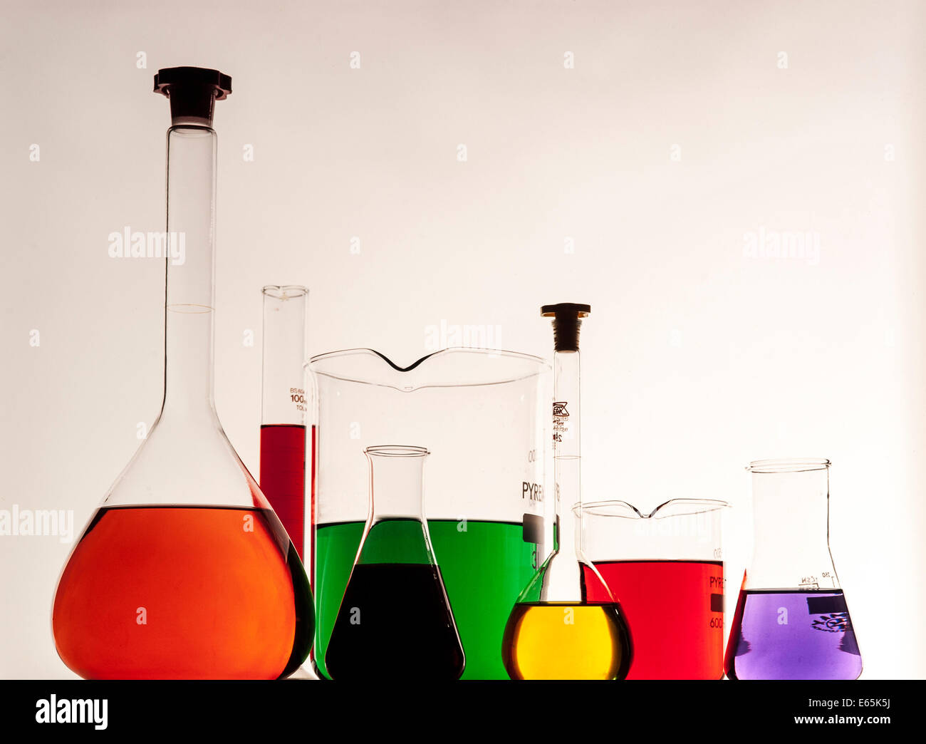 Chemical Flasks and Beakers with coloured fluids - Stock Image