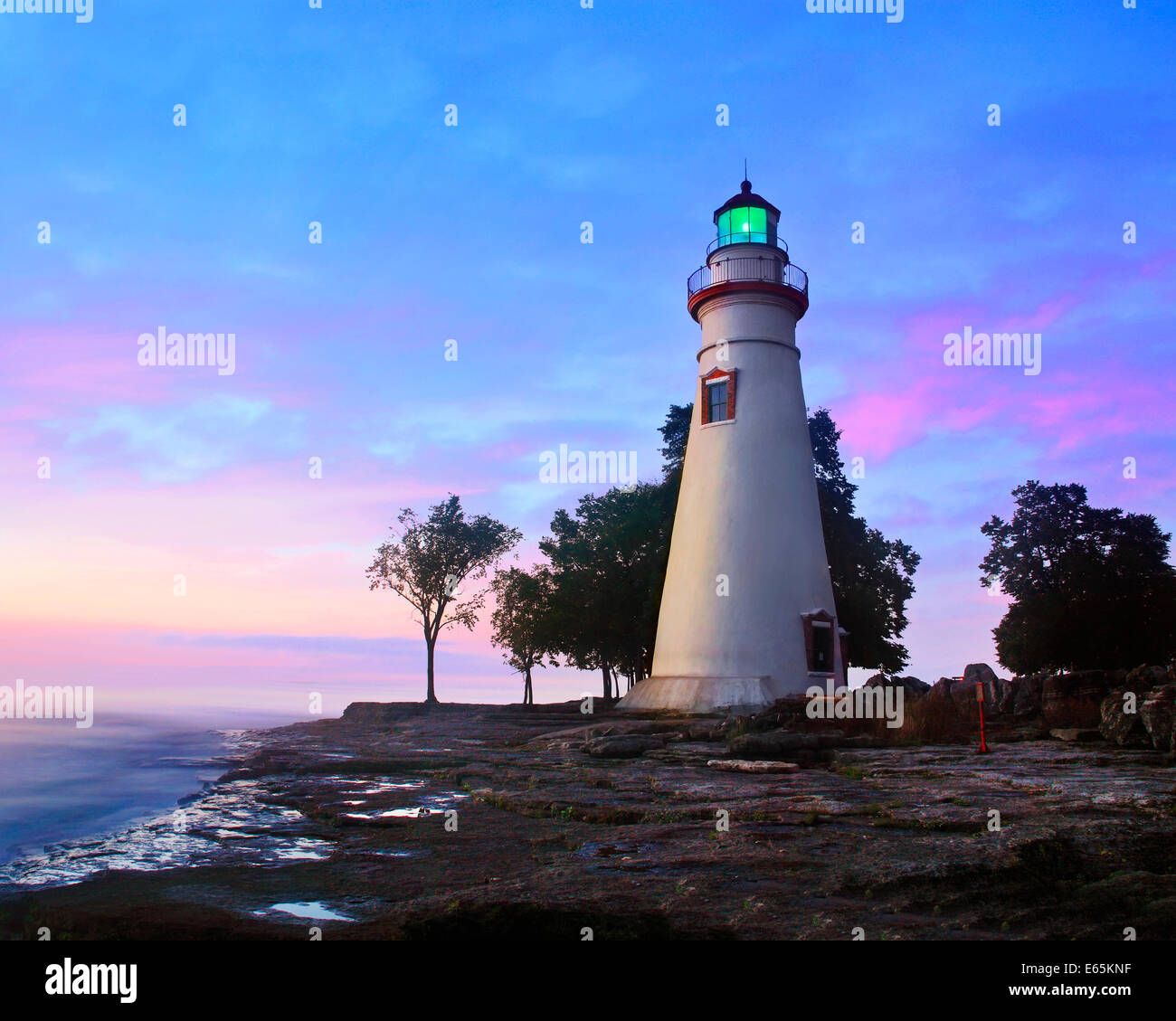 The Marblehead Lighthouse Radiates It's Green Light As The Sun Warms The Eastern Sky At Marblehead Ohio On Lake - Stock Image