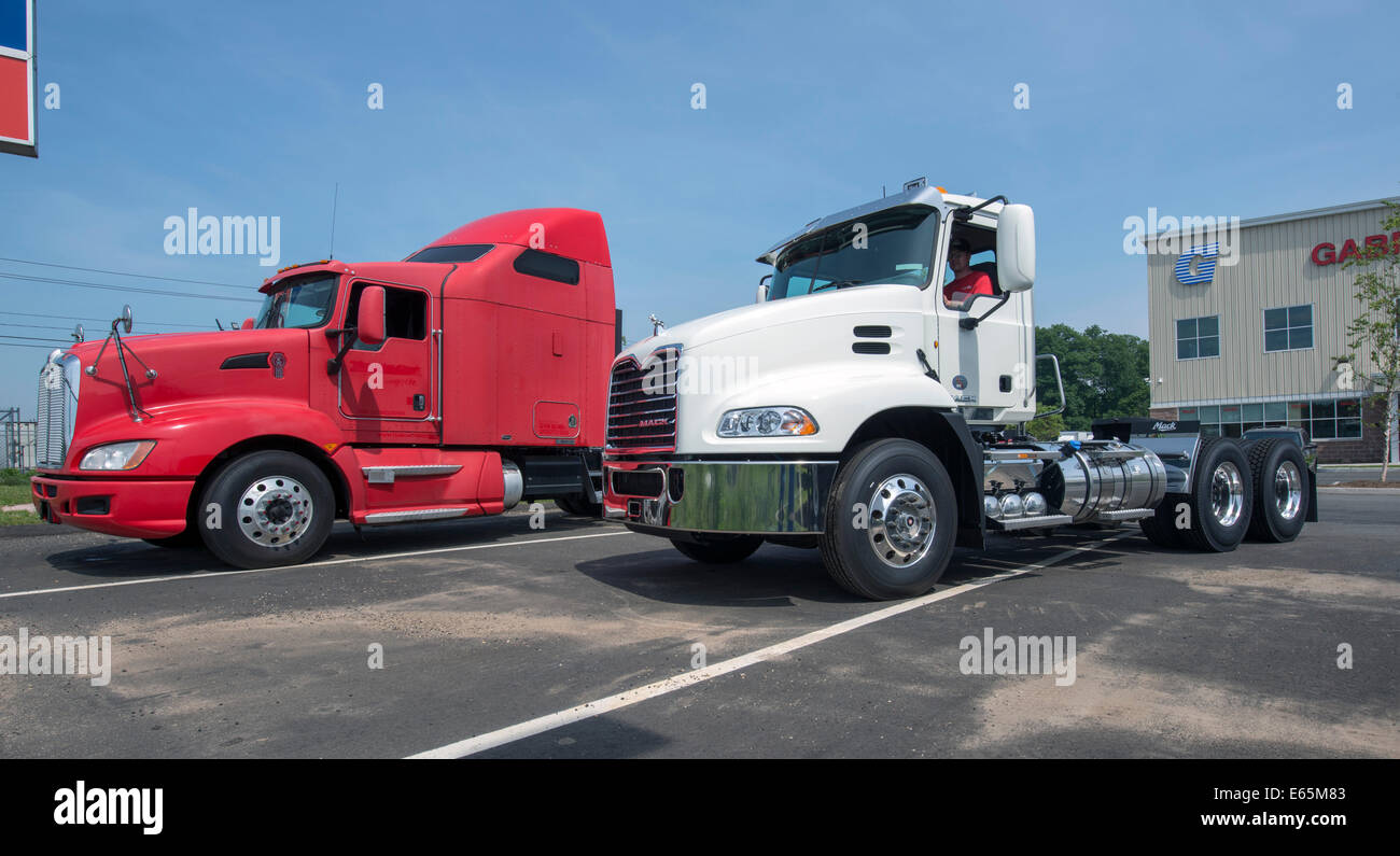 Tractor trailer truck cabs for sale.  Red one, with sleeper attached, is a Kenworth, white one a Mack. - Stock Image