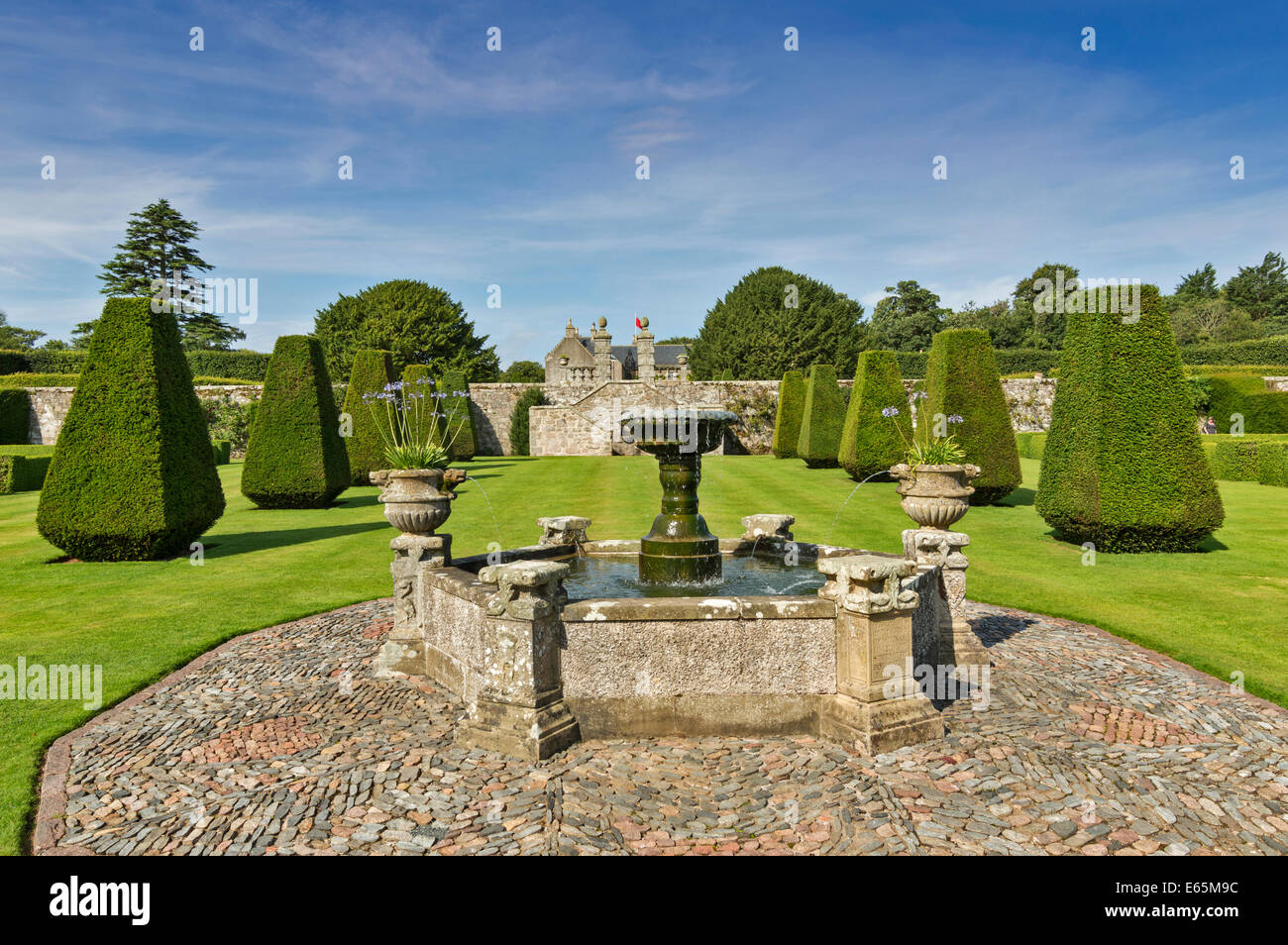 PITMEDDEN GARDENS ABERDEENSHIRE SCOTLAND WITH A LARGE FOUNTAIN AND THE TOPIARY AVENUE OF CLIPPED YEW BUSHES - Stock Image