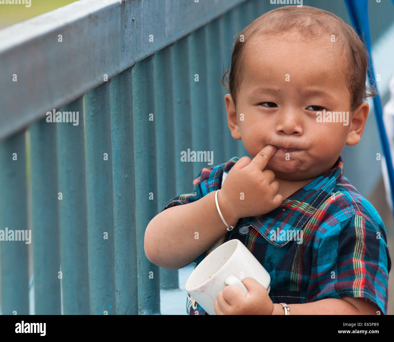 Funny young Nepalese child is waiting for a flight at Pokhara airport - Stock Image