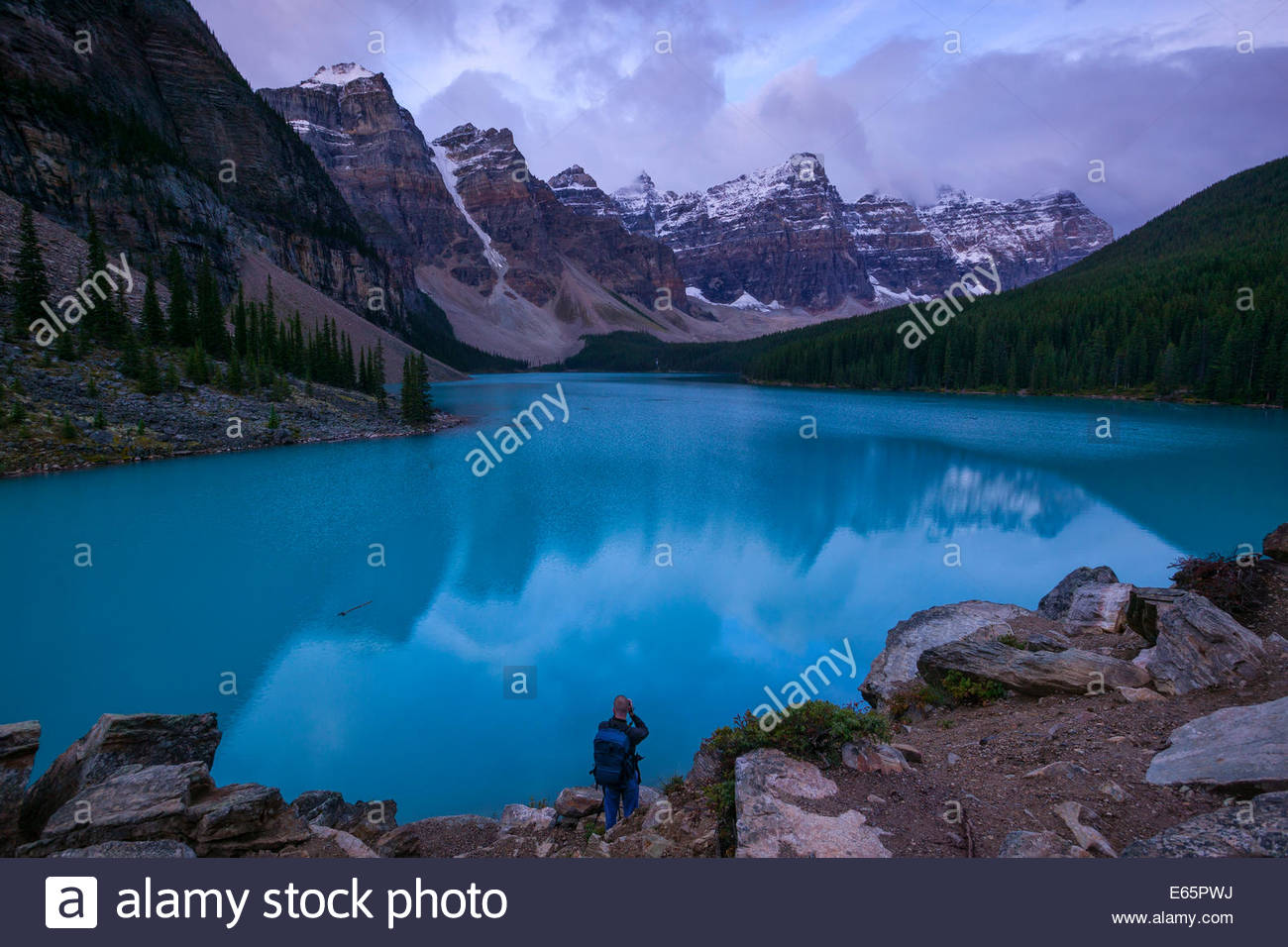 A man photographs the morning light on the mountains surrounding Moraine Lake in Banff National Park, Alberta, Canada. - Stock Image