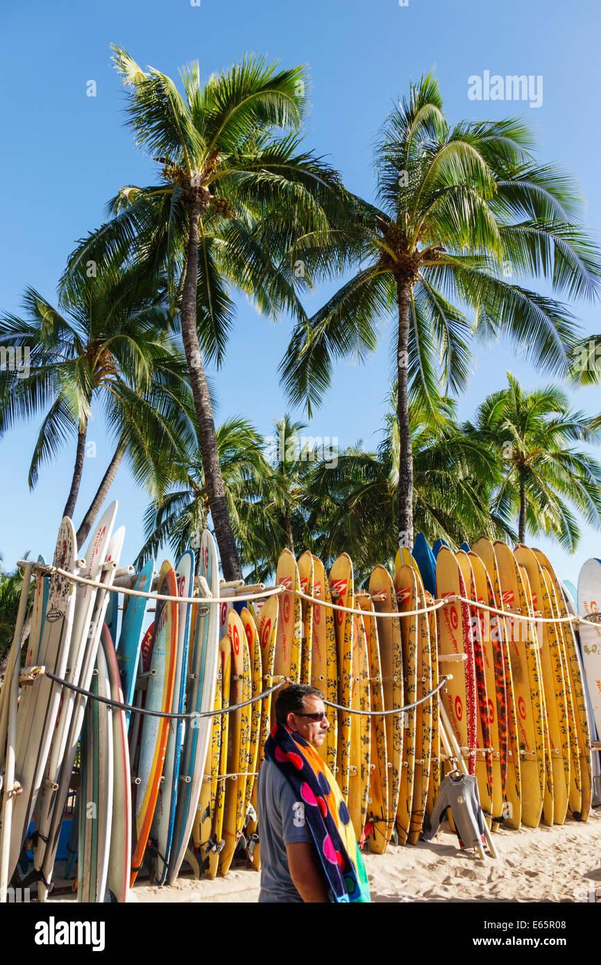 Hawaii Hawaiian Honolulu Waikiki Beach resort Kuhio Beach State Park rental surfboards rent palm trees man sunbather - Stock Image