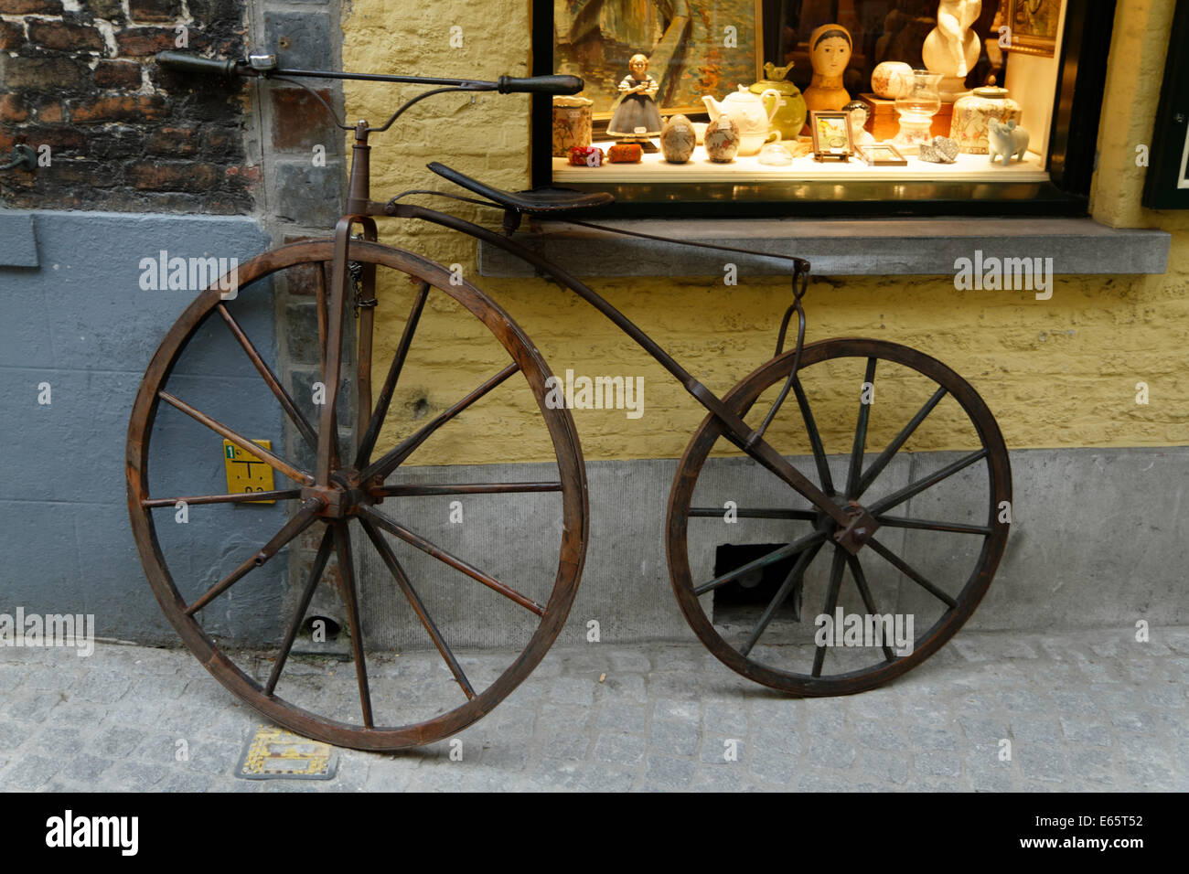 A 19th-century bicycle leans against an  antique shop wall and its illuminated window in Bruge - Stock Image